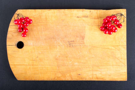 guelder rose berry: Viburnum berries on old worn out cutting board on the black background. Space for text. Billet for postcard.