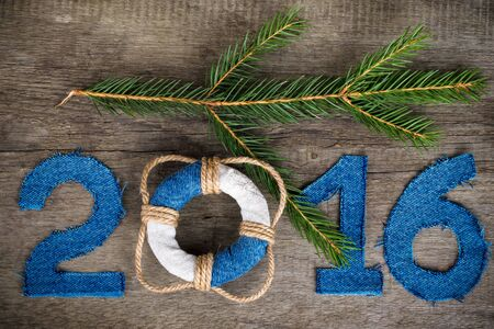 billet: Figures 2016 on old grey wooden background in sea style with wood, denim and rope material. Christmass theme. Billet for postcard or calendar. Toned.