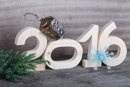 pack string: Wooden figures 2016, a branch of the Christmass tree, the plastic snowflake and old crashed Christmas toy on gray wooden background in retro vintage style. Stock Photo