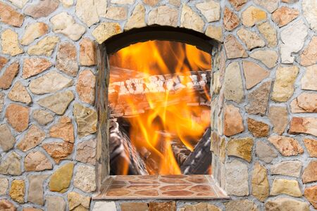 stone fireplace: The reflection of the real fire in a mirror decorative stone fireplace in comfortable living room.