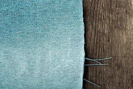 two and a half: Textured background of two materials - half is blue jeans and half is old grey wooden board. Toned.