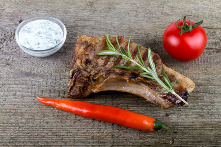 souse: Hot grilled meat with vegetables and creamy souse on old grey wooden board for background. Stock Photo