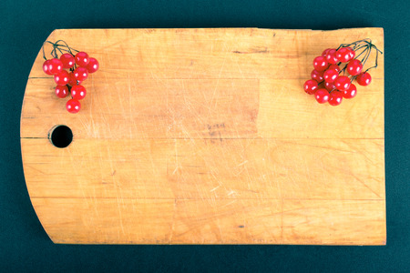 billet: Viburnum berries on old worn out cutting board on the black background. Space for text. Billet for postcard. Toned.