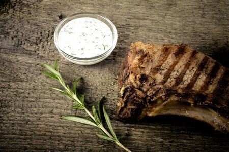 souse: Hot grilled meat with vegetables and creamy souse on old grey wooden board for background. Toned.