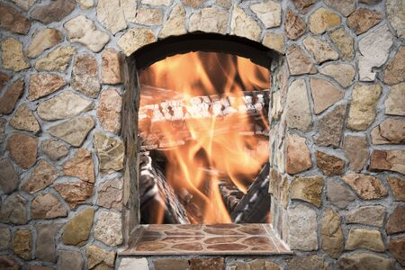 stone  fireplace: The reflection of the real fire in a mirror decorative stone fireplace in comfortable living room. Toned.
