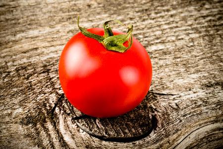 tomato: Fresh, red, ripe tomato on old grey wood background. Toned.