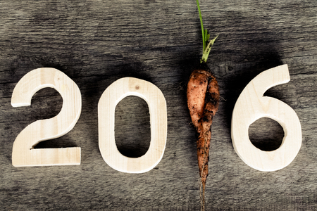 2016 on old grey wooden background with dirty fresh carrot instead digit 1 (one).