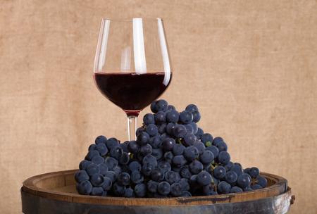 racimos de uvas: Barril, la copa con un poco de vino tinto y las uvas maduras de vino en el fondo de arpillera.