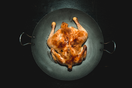 chiken: Fried chiken on a pan on a black wooden table. Toned.