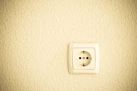 electric outlet: Light plastered wall with electric outlet for background.
