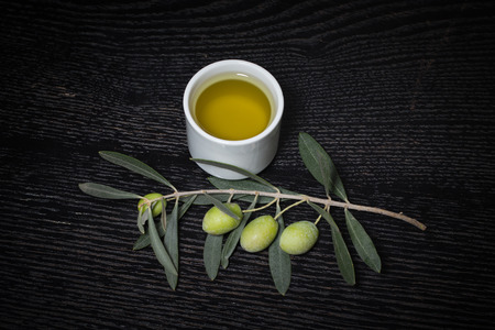 sun oil: Branch of olive tree with green olive berries and cap of fresh olive oil on a black wooden table or board. Toned.