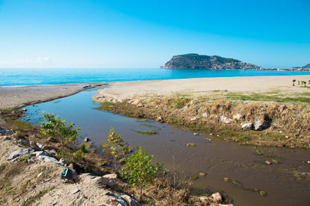 Confluence of the mountain river in the sea on beach in Alanya Turkey.