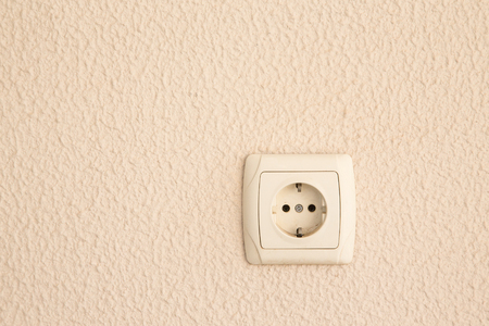 parget: Light plastered wall with electric outlet for background. Close up detale.