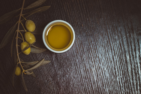 extra virgin olive oil: Branch of olive tree with green olive berries and cap of fresh olive oil on a black wooden table or board. Toned.