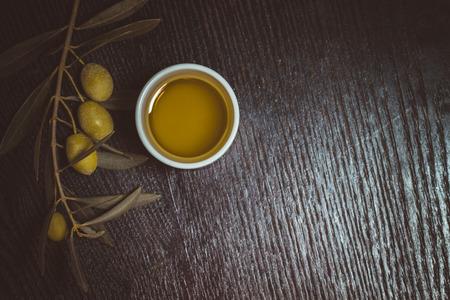 Tak van de olijfboom met groene olijven bessen en dop van verse olijfolie op een zwarte houten tafel of board. Afgezwakt.