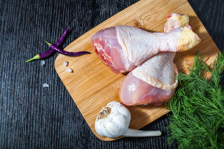 chiken: Fresh chiken legs on a black table or board like background. Toned.