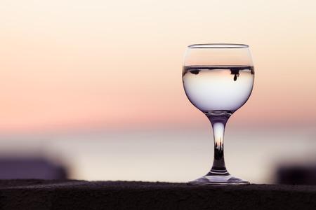 Glas witte wijn met reflecties van huizen en uitzicht op prachtige zonsondergang. Selectieve aandacht. Afgezwakt. Stockfoto