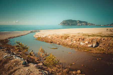 confluence: Confluence of the mountain river in the sea on beach in Alanya Turkey. Toned. Stock Photo