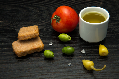 cooked pepper ball: Turkish traditional meal Kofte with vegetables and olive oil on black table. Selective focus. Stock Photo