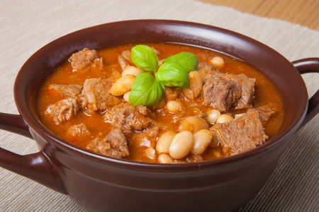 kuru: Traditional turkish meal - Kuru fasulye in a clay bowl on a light wooden table.