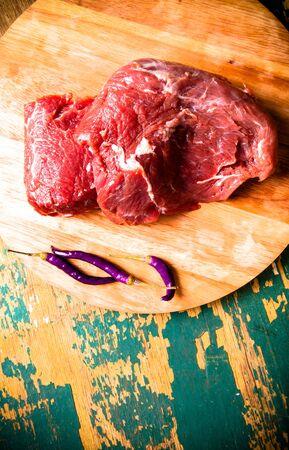 kuru: Fresh raw meat on light cutting board on an old wooden table. Ingredients for traditional turkish meal - Kuru fasulye. Toned.
