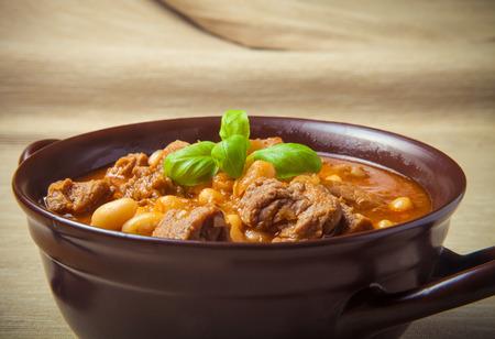 kuru: Traditional turkish meal - Kuru fasulye in a clay bowl on a light wooden table. Toned. Stock Photo