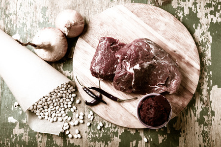 kuru: Fresh raw meat, white bean and vegetables on an old wooden table. Ingredients for traditional turkish meal - Kuru fasulye. Toned. Stock Photo