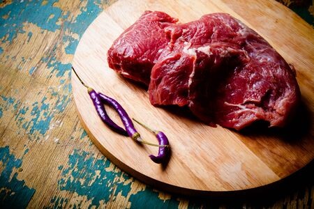 steak grill: Fresh raw meat on light cutting board on an old wooden table. Ingredients for traditional turkish meal - Kuru fasulye. Toned.