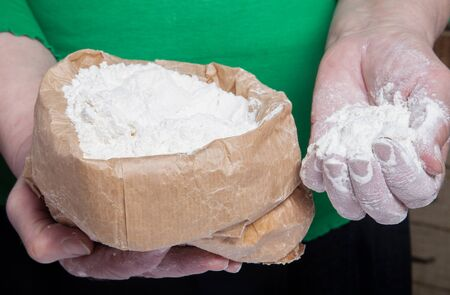 woman's hand: Flour in the womans hand. Selective focus. Stock Photo