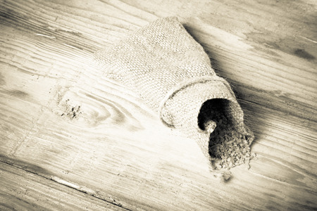 malted: Groat pours out of the bag on a wooden table made of old boards. Toned. Stock Photo