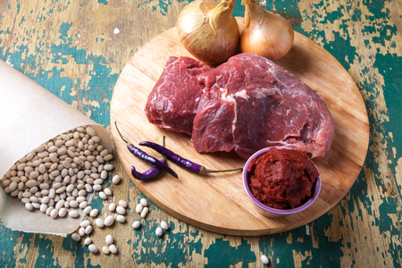 kuru: Fresh raw meat, white bean and vegetables on an old wooden table. Ingredients for traditional turkish meal - Kuru fasulye.