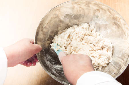 knead: Womans hands knead dough. Selective focus. Toned. Stock Photo