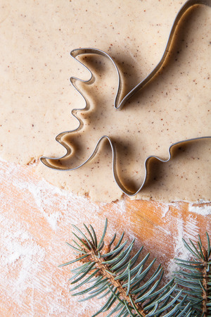gingerbread cookie: Dough for gingerbread cookie and cookie cutters in different shapes on light wooden cutting board like background.