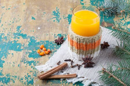 Glass of sea buckthorn beverage (kissel) on a napkin on old wooden table or board for background. New year theme.
