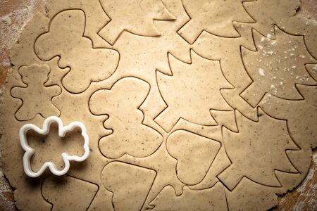 gingerbread cookie: Dough for gingerbread cookie and cookie cutters in different shapes on light wooden cutting board like background. Toned. Stock Photo