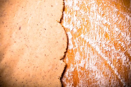 gingerbread cookie: Dough for gingerbread cookie on light wooden cutting board like background. Toned.