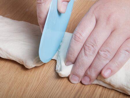 cut up: Female hands cut up dough. Selective focus.