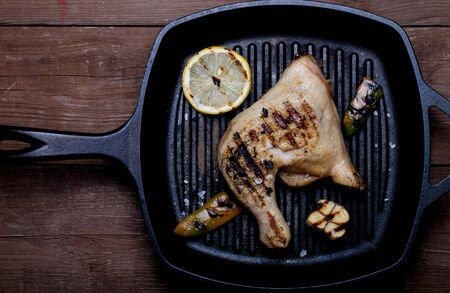 chiken: Chiken and vegetables on grill pan on old wooden table or board.