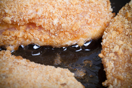 bleu: Chicken cordon bleu fried in oil in a frying pan. Selective focus. Toned. Stock Photo