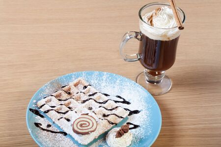 strew: Traditional belgium soft fresh waffles with a decor on a plate and cup of coffee with whipped creams. Stock Photo