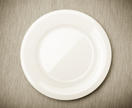 Empty white plate on grey napkin, top view. Toned.