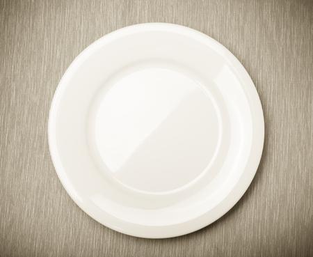 Lege witte plaat op grijs servet, bovenaanzicht. Afgezwakt. Stockfoto