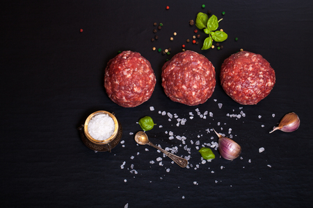 Raw ground beef meat steak cutlets with herbs and spices on black table or board for background. Selective focus.