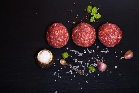 Surowe mięso kotlety wołowe mielony stek z ziół i przypraw na czarnym stole lub płycie na tle. Selektywne fokus. Zdjęcie Seryjne