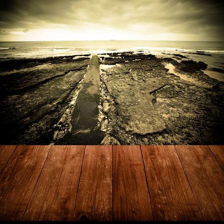 View of the embankment at low tide from dark wooden gangway or bridge. Collage. Estoril, Lisbon, Portugal. Dramatic view. Toned.