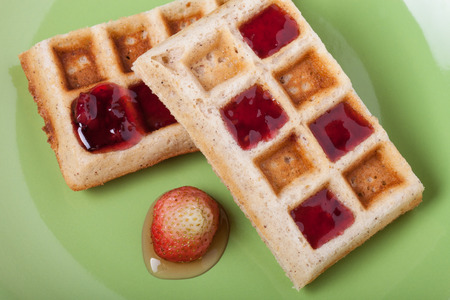 strew: Traditional belgium soft fresh waffles with a decor on a plate.