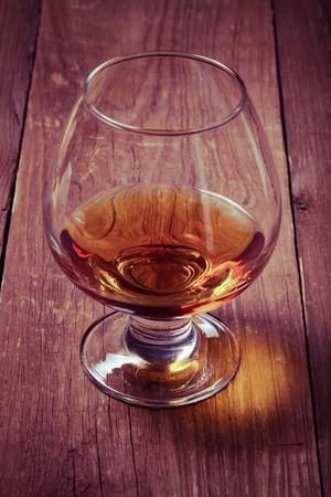 drunks: Cognac in a glass goblet on the old wooden table. Toned.