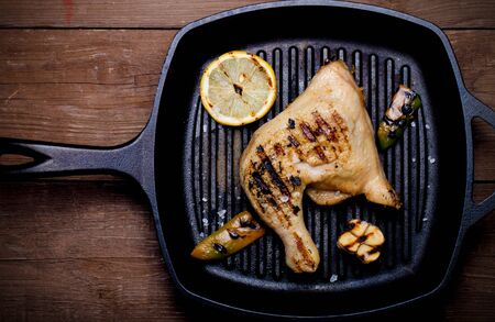 chiken: Chiken and vegetables on grill pan on old wooden table or board. Toned. Stock Photo