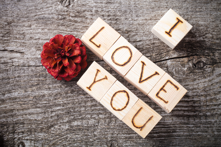 love confession: Romantic inscription of letters on light wooden cubes on a old grey wooden background. Toned.