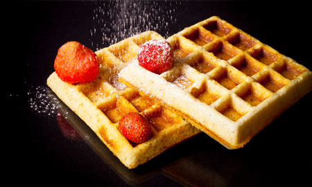 waffle: Traditional belgium soft waffles with strawberries and powdered sugar on black background. Toned.